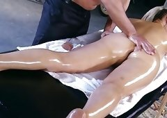 Oiled-up brunette fucked on a massage table