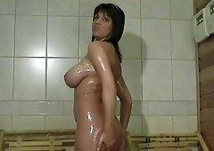 Hot brunette babe with big tits bathing and oils up her body