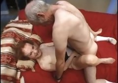 Redhead shabby white grandma on her knees blowing two dicks