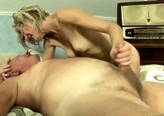 Short-haired blondie deepthroating a small cock on a fancy bed