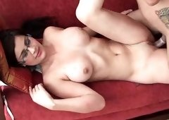 A chick with glasses and large tits is fucked on the sofa